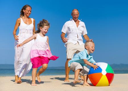 Familia jugando a la pelota en la playa.