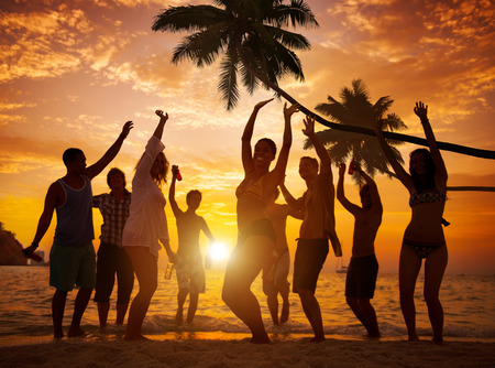 group: Diverse People Dancing and Partying on a Tropical Beach Stock Photo