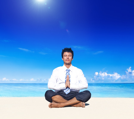 hunker: Businessman meditating on the beach. Stock Photo
