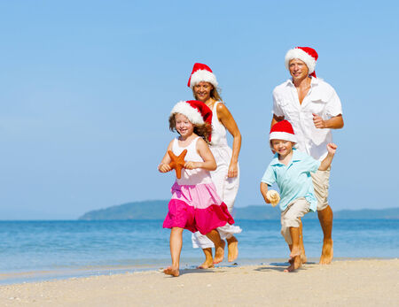 Family running on the beach in Christmas.
