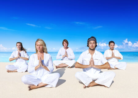 yoga class: People performing yoga on the beach. Stock Photo