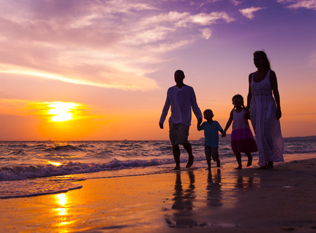 purple sunset: Family walking on the beach. Stock Photo