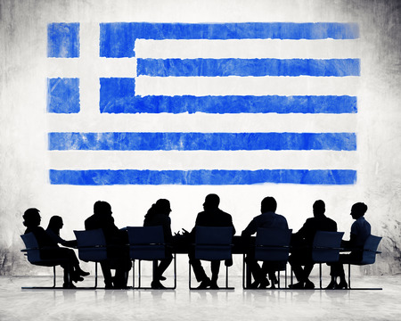 Silhouettes of Business People and a Flag of Greece photo
