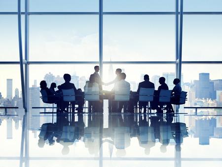 estrechando mano: Silueta de Personas de negocios en una sala de juntas