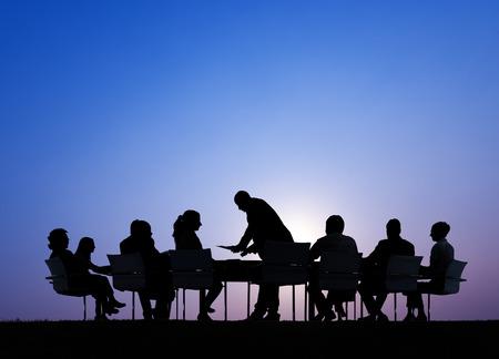 meeting people: Siluetas de hombres de negocios en una reuni�n al aire libre