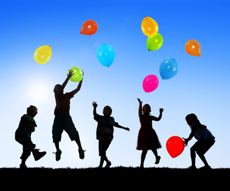 children playing: Silhouettes of Cheerful Children Playing Balloons Outdoors
