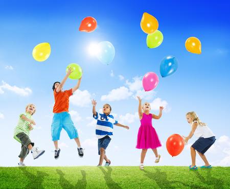 niños jugando en el parque: Multiétnico Niños Jugando Al Aire Libre Globos Juntos