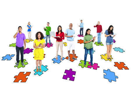 Group of multi-ethnic people standing on pictures of puzzle pieces wth their electronic devices. photo
