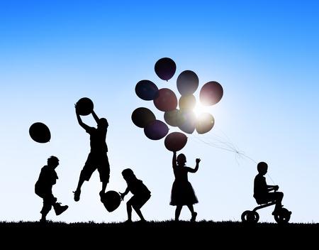 Silhouetten van spelende kinderen Ballonnen en Riding Bicycle Stockfoto