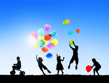 Silhouettes of Children Playing Balloons Outdoors photo