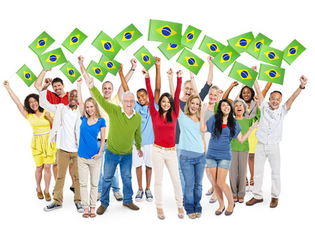south asian ethnicity: Cheerful Multi-Ethnic Group Of People Standing With Their Arms Raised Holding Brazilian Flag.