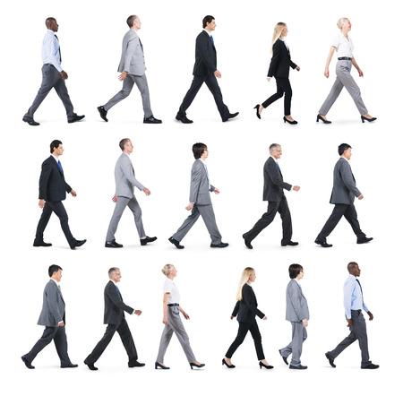 menschen unterwegs: Gruppe Geschäftsleute, die zu Fuß in eine Richtung Lizenzfreie Bilder