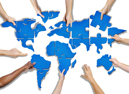business connection: Group of Hands Holding Jigasw Puzzle Forming World