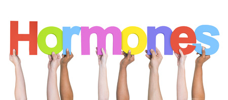hormonal: Group of Multiethnic Hands Holding Hormones Stock Photo