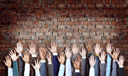 manos levantadas: Grupo de manos de negocios diversos Criado en la pared de ladrillo Foto de archivo