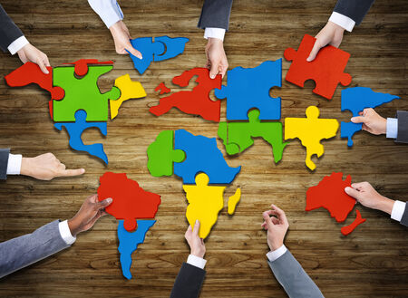 forming: Aerial View of People Forming World Map with Puzzle Pieces