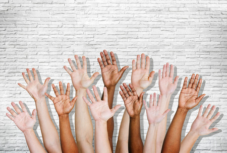 Group of human arms raised with brick wall. photo