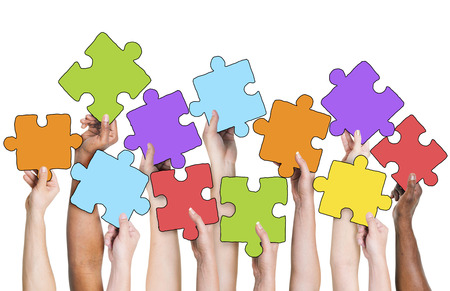 Ludzkiej dłoni trzymającej Kolorowe Jigsaw Puzzle Pieces