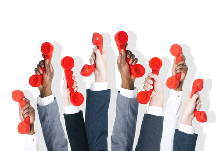 customer service phone: Business people holding red phone.