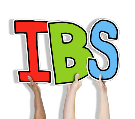 constipated: Group of Hands Holding IBS Letter