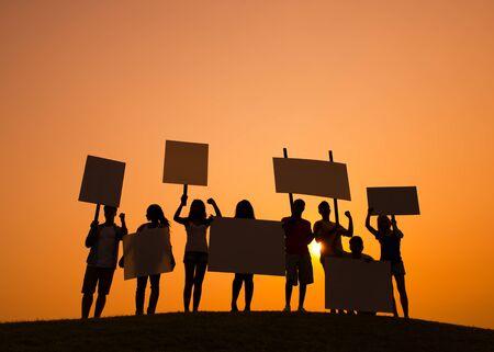 conflictos sociales: Silueta de personas que protestaban en la puesta del sol