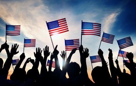 Menschengruppe Wellenartig bewegende amerikanische Flaggen in Gegenlicht Standard-Bild - 35336814