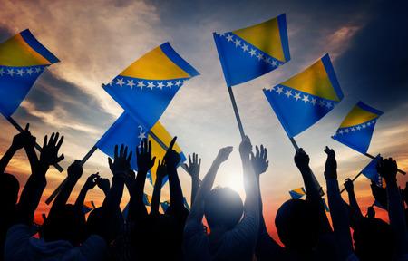 hercegovina: Silhouettes of People Holding Flag of Bosnia and Herzegovina