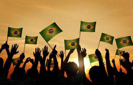 personas saludando: Grupo de personas que ondeaban banderas de Brasil Contraluz