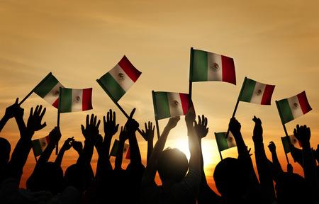 gente saludando: Grupo de personas que ondeaban banderas mexicanas en Contraluz