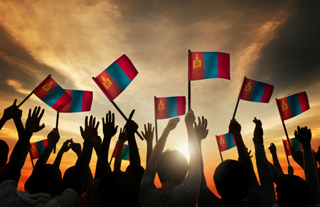 gente saludando: Grupo de personas que ondeaban banderas de Mongolia en Contraluz