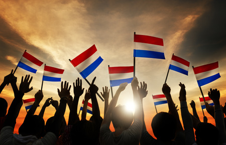 netherlands flag: Silhouettes of People Holding Flag of Netherlands Stock Photo