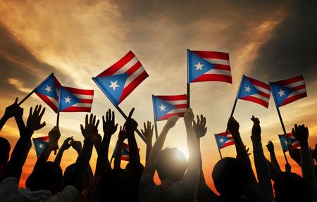 Group of People Waving Flag of Puerto Rico in Back Lit 写真素材