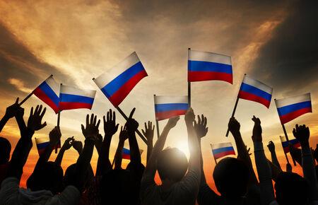 personas saludando: Grupo de personas que ondeaban banderas de Rusia en Contraluz