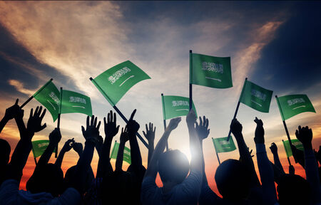 national flag: Silhouettes of People Holding Flag of Saudi Arabia