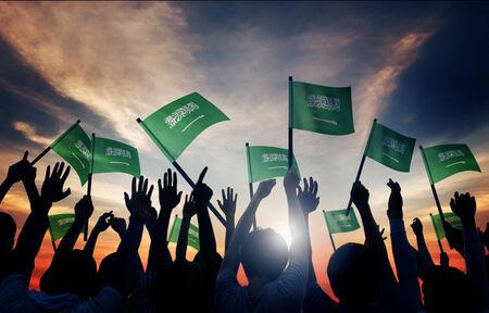 Silhouettes of People Holding Flag of Saudi Arabia