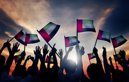 Gruppe von Personen, Wellenartig bewegende Flagge der Vereinigten Arabischen Emirate in Gegenlicht Standard-Bild - 35336890