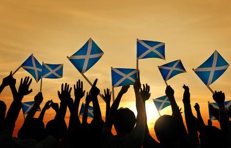 gente saludando: Grupo de personas que ondeaban banderas escocesas en Contraluz Foto de archivo