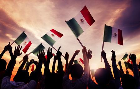bandera de mexico: Grupo de personas Holding Banderas Nacionales de México Foto de archivo