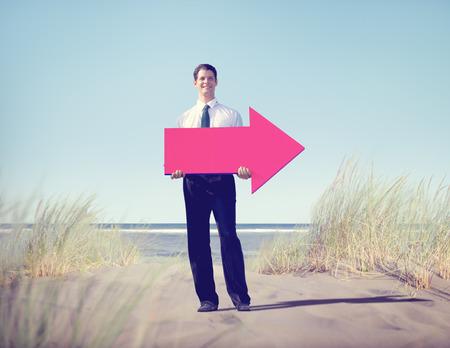 Businessman holding arrow on beach photo