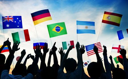 personas saludando: Grupo de personas que ondeaban banderas nacionales en Contraluz