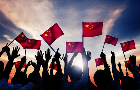 Silhouettes of People Holding the Flag of China photo