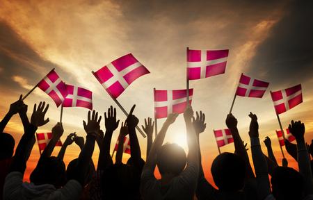 manos levantadas al cielo: Siluetas de personas que tienen la bandera de Dinamarca Foto de archivo