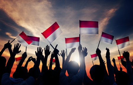 celebrations: Silhouettes of People Holding the Flag of Indonesia Stock Photo