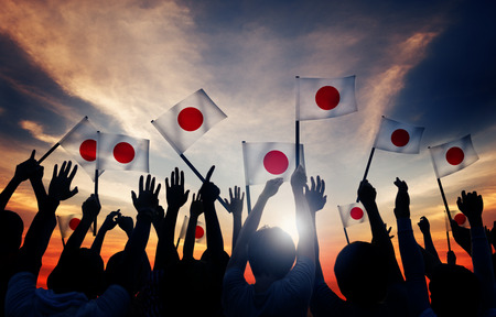 Silhouettes of People Holding the Flag of Japan photo