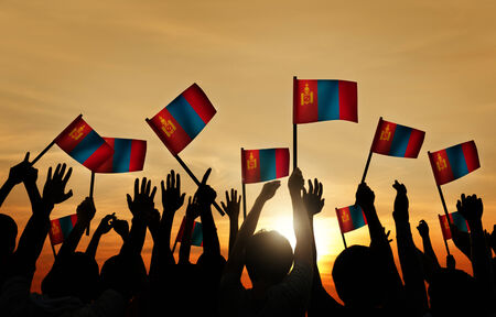 Group of People Waving Mongolian Flags in Back Lit photo
