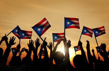 gente saludando: Grupo de personas que ondeaban la bandera de Puerto Rico en Contraluz