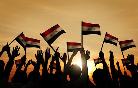 gente saludando: Grupo de personas que ondeaban la bandera de Siria en Contraluz