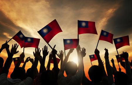 gente saludando: Grupo de personas que ondeaban banderas taiwanesas en Contraluz Foto de archivo