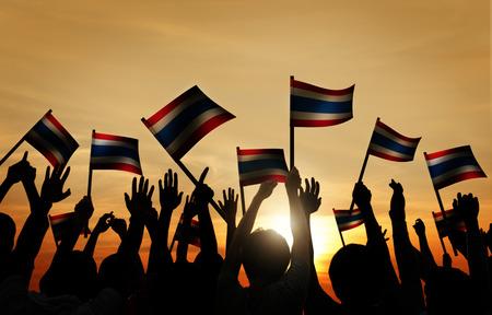 personas saludando: Grupo de personas que ondeaban la bandera de Thailalnd en Contraluz
