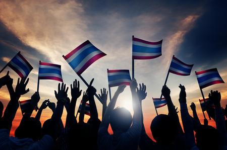 personas saludando: Grupo de personas que ondeaban la bandera de Tailandia en Contraluz